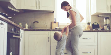 A mom cooking with her young son at home with work-at-home jobs for stay-at-home moms.