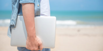 Man hand a holding laptop at the beach.