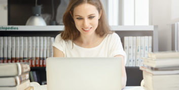 Woman on laptop looking for companies hiring for online tutoring jobs