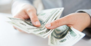 Hands with money getting paid for work-from-home jobs that can pay $100,000 or more.