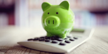 A green piggy bank on a calculator.