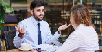 Man shrugging trying to figure out how to honestly answer a tricky job interview question.