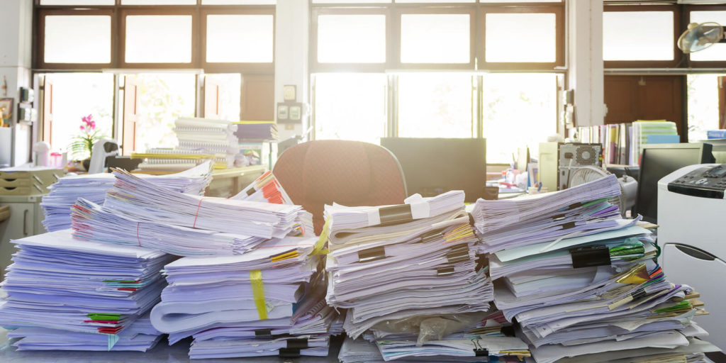 Unorganized desk representing how not to organize a job search.