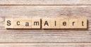 Scam alert word written on wood block