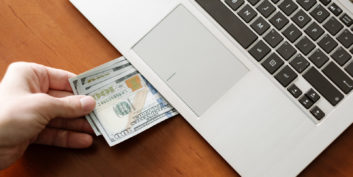 Money under laptop for high-paying remote tech jobs