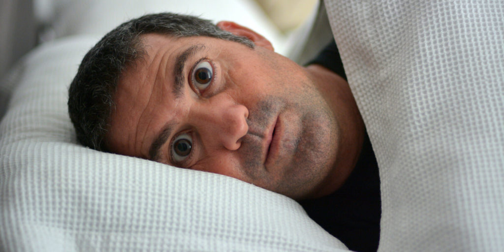 Man experiencing sleeplessness from work anxiety