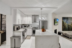 Open custom kitchen with gas stove top, Caesarstone quartz countertops and waterfall center island featuring bar seating