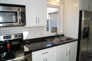 New stainless appliances, cabinets, counter, sink and faucet
