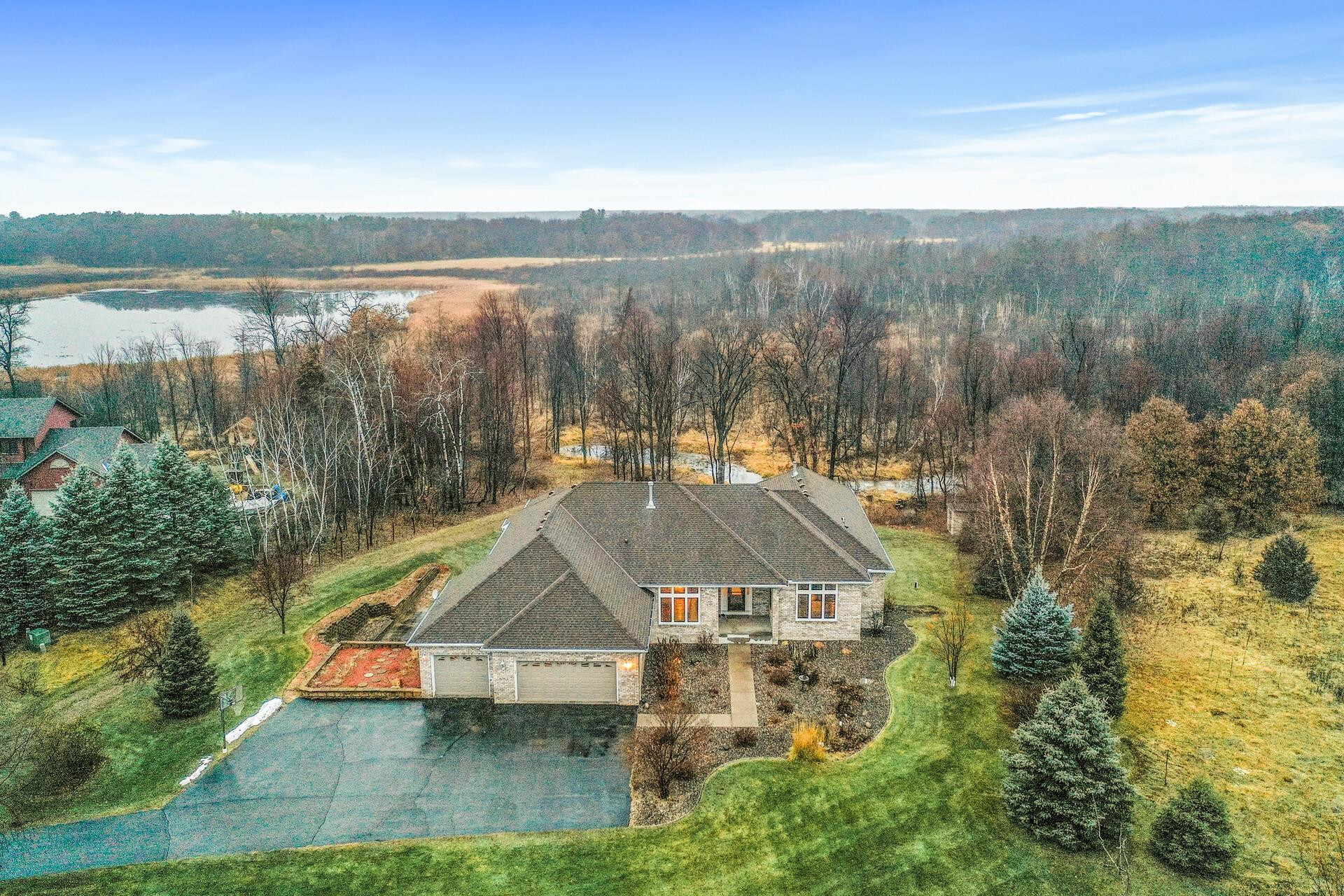The property extends back into the wooded area toward the large pond in back.