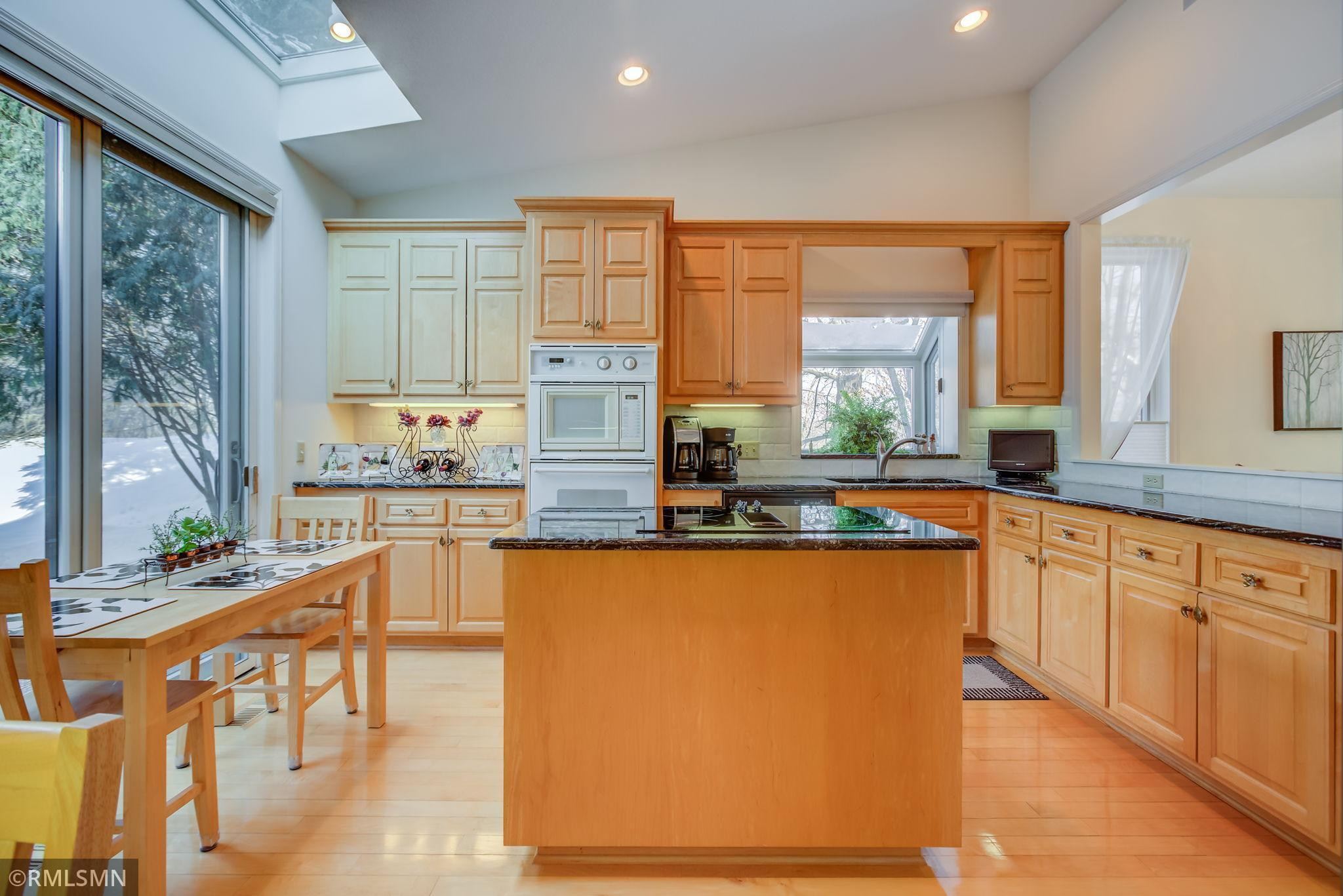 Bright & sunny Eat-In Kitchen, Maple Floors and Cabinets, Granite Countertops, Granite-Composite Sink, and Plenty of Storage.