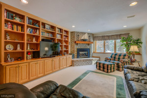 Lower level with gas burning fireplace, full wall of built ins and look out windows.