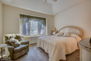 Master bedroom with trayed ceiling, window bench and fan