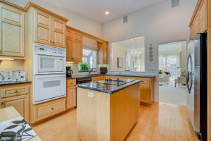 Cooktop Stove in Granite-Topped Island. Stainless Steel Refrigerator and Pass-Through Window to dining Room