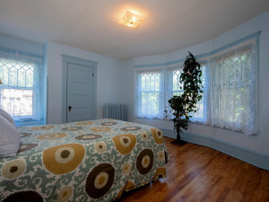 First of four spacious bedrooms on upper level has southern exposure. Curved wall of windows.
