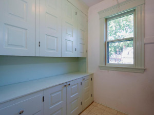 Walk-in Pantry has plenty of storage. Solid wood cabinets. Wood shelving on opposite side.