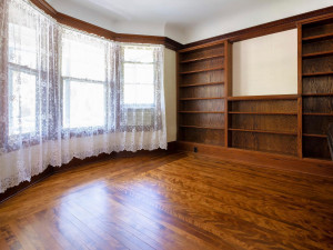 Adjacent to the living room is this library/family room that offers a wall of built-in shelving. Bay windows allows for a sun filled room. Look at the coved ceilings. Amazing!