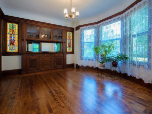Gorgeous formal dining room with a built-in buffet with leaded glass, flanked by original stained glass windows and bay windows. Timeless mill work you just don't see very often.