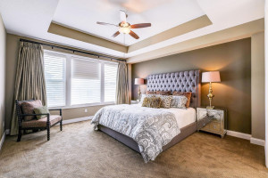 Impressive master suite has high, tray ceilings and...