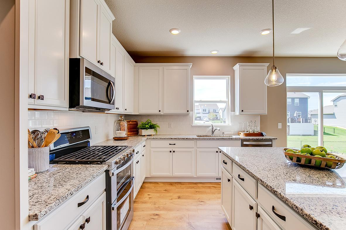 Stainless steel appliances along with granite countertops are highlights of this open kitchen space. *photos are of model home, finishes in actual home may vary.