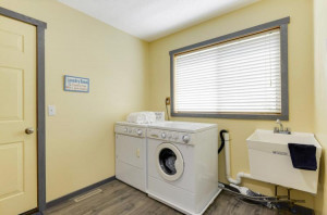 An 8x8 large laundry room in the back entry on main from the garage is so adorable! Plenty of room for the boot tray and a huge coat closet for coats and more!