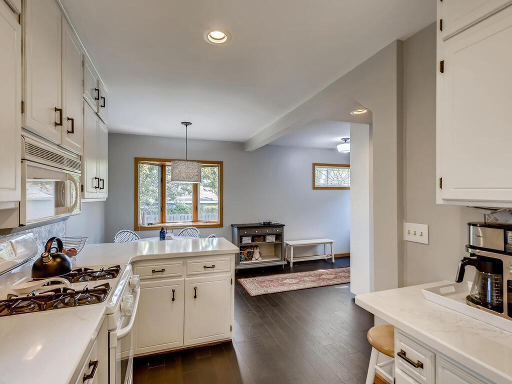 Renovated kitchen with quartz countertops, luxury vinyl floor and adjoining mudroom