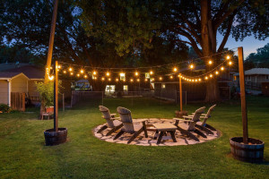 Enjoy the ultimate yard with two patios. This one has firepit and lights for evening get togethers.