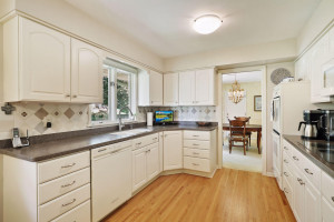 Kitchen with hardwood floors & window overlooking private, flat backyard.