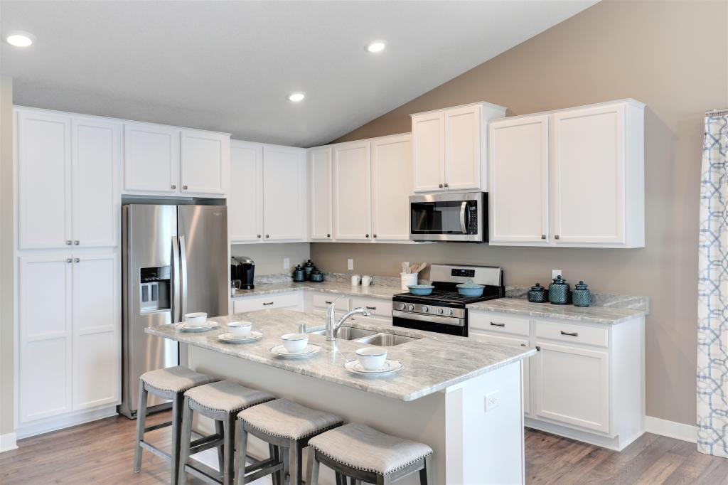 The Everett is a 4 bed, 3 bath and 3 car garage home. Beautiful maple cabinetry and stunning granite make this kitchen a dream come true. Photo of a completed model home. Some colors/options may vary.