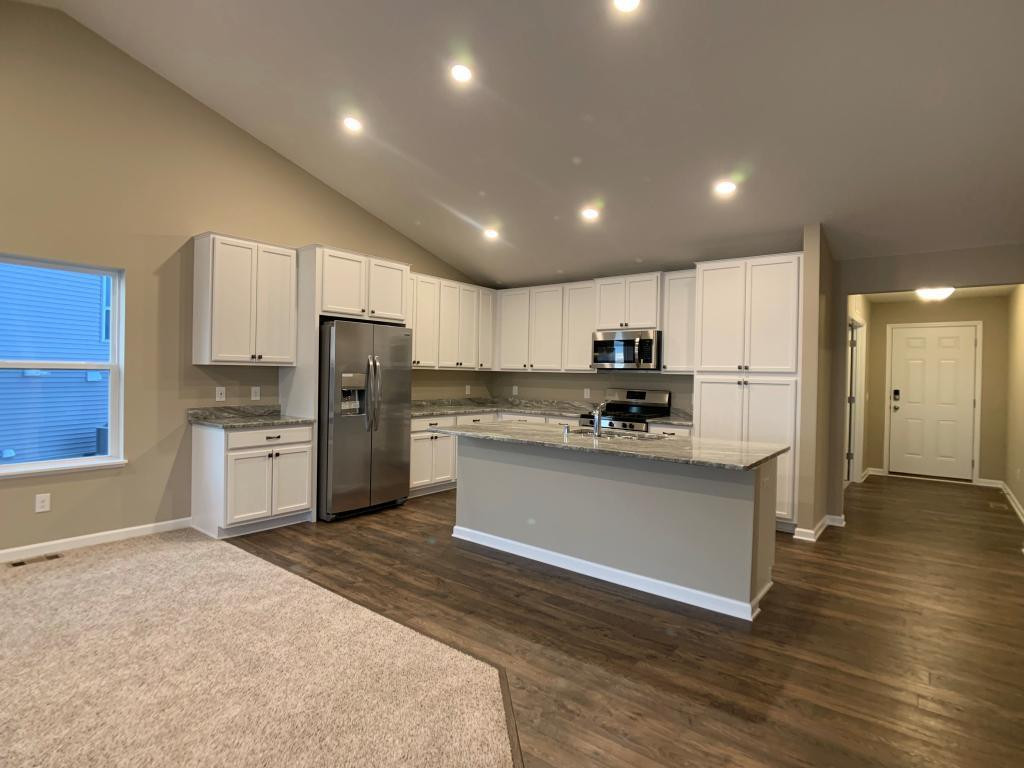 The heartbeat of the kitchen - this island has loads of counter space all coated in granite countertops!! Photo of previous spec home. Floorplan has been modified to include corner pantry and relocate sink.
