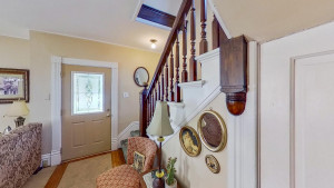 Front Entryway Features Open Staircase and Natural Woodwork