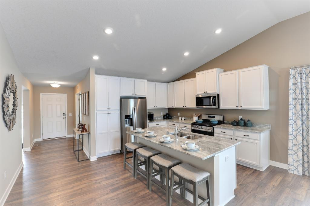 The Everett is a 4 bed, 3 bath and 3 car garage home. Beautiful maple cabinetry and stunning granite make this kitchen a dream come true. .. Photo of a completed model home. Some colors/options may vary.