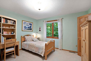 Bedroom 3 has a view of the wooded backyard.