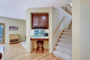 Dual stairs from kitchen leads to the upper level. Small desk and cabinetry to organize home and family is located in this nook.