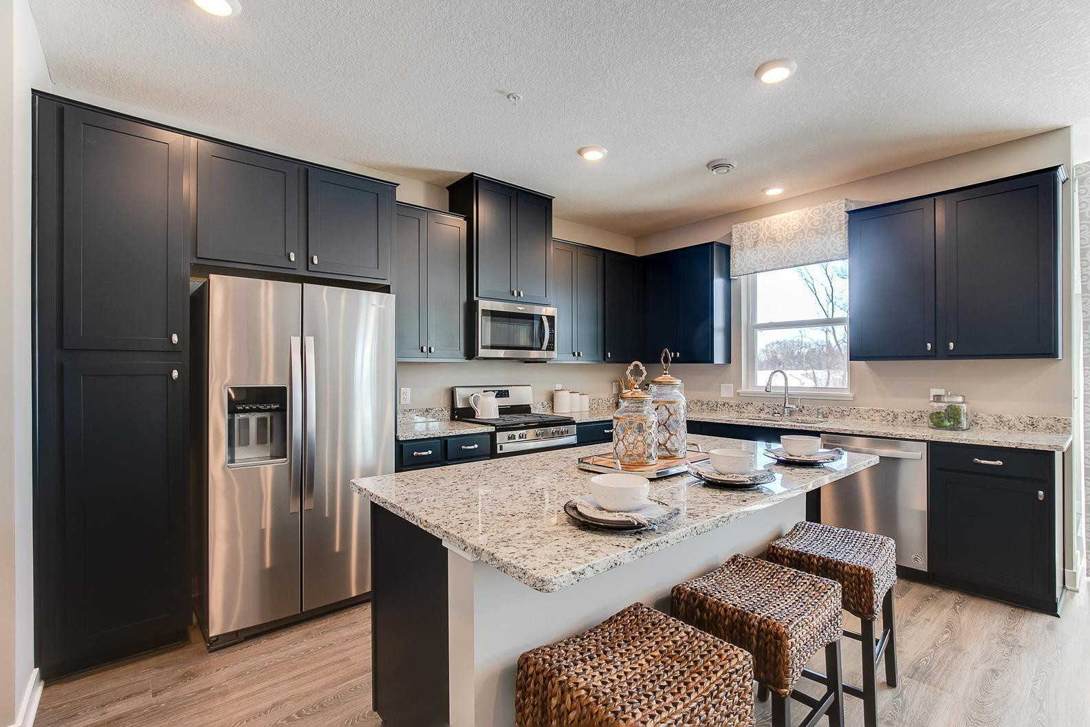 Open-and inviting, the home's living spaces flow seamlessly out from the kitchen - a theme consistent throughout the entire layout!! Pictures are of the decorated model.