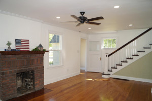 Large living room with cove trim, open stairway
