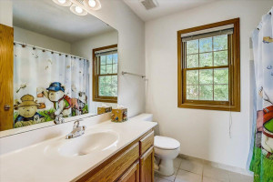 Full shared upper level bathroom with tile floors and backyard views.