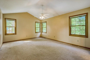 Upper level Master Suite is roomy with a 10-foot vaulted ceiling, side and backyard views, and walk-in closet.