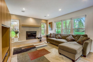 Spacious sun-filled living room features a cozy wood-burning fireplace for added warmth & ambiance with tiled wall surround, built-in wood mantle + side and backyard views.