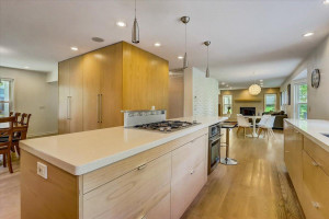 Open main level floor plan with hardwood floors, recessed lighting, roller shades, built-in surround sound and stylish light fixtures.