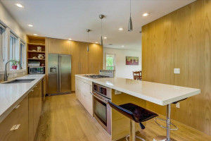 Beautiful modern contemporary kitchen is expansive with sparkling countertops, abundant storage, pull out cabinets, stainless-steel appliances, large center island with breakfast bar seating, and wall of windows with gorgeous backyard views.