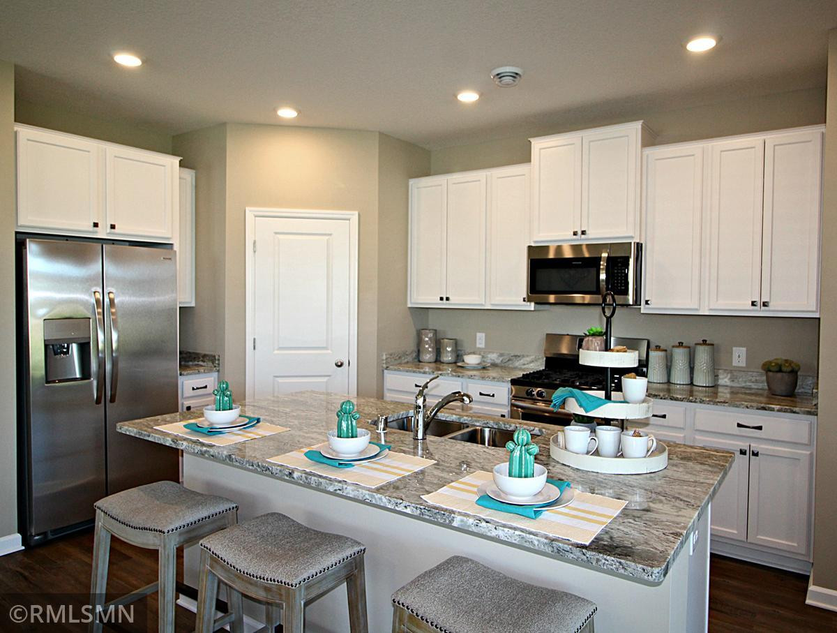 Thoughtfully-designed, modern and fresh describes this kitchen. Equipped with stainless steel appliances, granite countertops and a large island, this kitchen adds distinction and character to the home. Photo of model, colors will vary