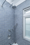 Waterfall shower with beautiful subway tile surround.