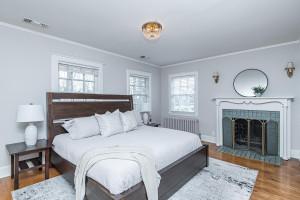 Master bedroom with elegant wood-burning fireplace and hardwood floors.