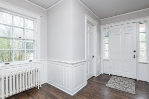 Spacious and elegant foyer with hardwood flooring and a large closet on one side and half bath on the other.