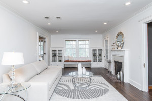 Amazing living room with crown moulding, recessed lighting, window bench, fireplace, hardwood flooring, and built-ins!