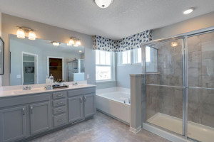 An extension of the primary suite, this private and spacious bathroom contains a double-vanity, a separate shower and tub, a private water closet, plus two walk-in closets. *pictures are of model home, actual colors may vary.