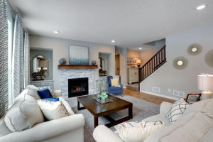 The home's main level family room features a natural gas fireplace and matching built-in entertainment cabinets. *pictures are of model home, actual colors may vary.