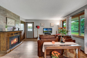 The Welcoming Entry Leads to the Living Room with it's Large South Facing Windows at Right and Moveable Electric Fireplace at Left. Notice the 24 x 12 Inch Accent Wall Tiles and Luxury Plank Flooring, Both New June 2021.