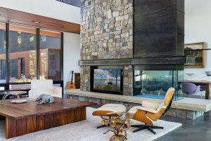 A custom-color, gas fireplace highlights the main living room, along with stone, skylights and wood inlays.