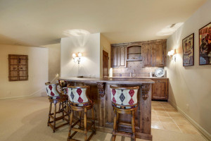 wet bar with storage room that has full size fridge